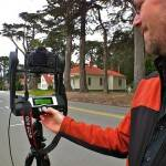 In front of historic houses on Funston Avenue at the Presidio of San Francisco, Michael Ashley demonstrates how the GigaPan robot works.